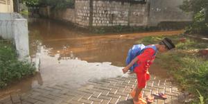 Anak Kecil usai pulang Mengaji Yang Sedang Mencopotkan Celana Untuk Melewati Air Yang Menggenang